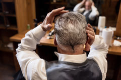 Back view of senior man styling his hair. Beautify yourself. Close up back view of senior gentle man styling his grey hair himself at barbershop Stock Images