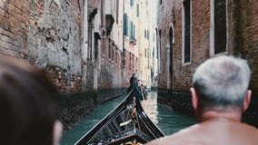 Back view of senior man and woman in gondola excursion tour on very narrow Venice canal in Italy during retirement trip. stock footage
