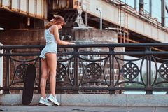 Back view of a sensual skater girl dressed in shorts and t-shirt leaning on the guardrail at a embankment. royalty free stock images