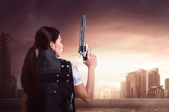 Back view of sexy asian woman using police uniform with gun. On the rooftop of building Royalty Free Stock Photo