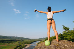 Back view of sexy brunette woman fitness instructor with perfect ass doing exercises with dumbbells and ball. Outdoor. Training concept. Green forest mountains Royalty Free Stock Images