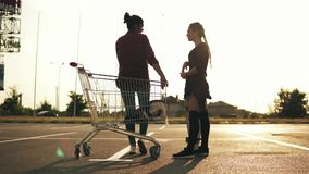 Back view of a girl in long socks and shorts holding a skateboard and talking to her girlfriend that is sitting on. The shopping cart in the parking near the stock video