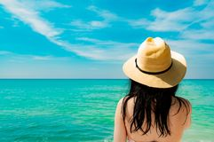 Back view of and happy young Asian woman wear straw hat relaxing and enjoy holiday at tropical paradise beach. Girl standing royalty free stock photos