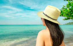 Back view of young Asian woman wear pink bikini, straw hat, and sunglasses relaxing and enjoy holiday at tropical paradise royalty free stock images