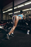 Back view of young girl resting in the gym and leaning on row of dumbbells stock photo
