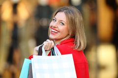 Shopper shopping holding bags looking at you. Back view of a shopper shopping holding bags looking at you on the street Royalty Free Stock Photo