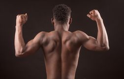 Afro sportsman flexing his muscles isolated on the black background royalty free stock image