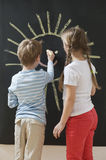 Back view of siblings drawing sun on blackboard Royalty Free Stock Photo
