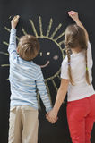Back view of siblings drawing sun on blackboard while holding hands Stock Image