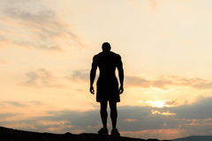 Back view on silhouette of bodybuilder posing at the sunrise or sunset in mountains. Handsome strong man showing his Royalty Free Stock Image