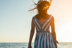 Back view silhouette of brunette beautiful woman walking along b. Each and sea sunset background. Cover idea. Female in dress walking on ocean, wind blowing hair Stock Photography