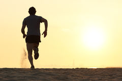 Back view silhouette of a runner man running on the beach. At sunset with sun in the background Stock Images