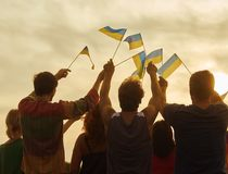 Back view, silhouette of ukrainian people with flags. Patriotic family against sunset background stock photo