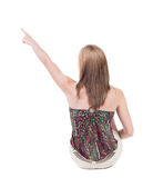 Back view of  sitting pointing woman. beautiful blonde girl. Royalty Free Stock Photo