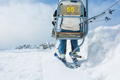 Back view of skier riding a lift. Royalty Free Stock Image