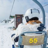Back view of skier riding a lift. Stock Images