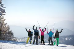 Back view of skiers on the top of the mountain. Back view of skiers with ski sticks up on the top of the mountain Stock Photography