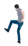 Back view of skinny guy funny fights waving his arms and legs. Stock Photo