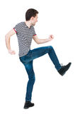 Back view of skinny guy funny fights waving his arms and legs. Stock Photography