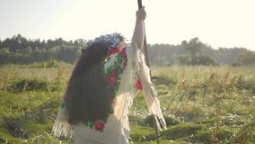 Back view of overweight woman in traditional shawl with a wreath on her head walking on summer field with the scythe. Back view of Slavic overweight woman in a stock video