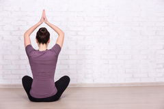 Back view of slim sporty woman doing yoga over white brick wall Stock Image