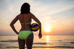Back view of slim woman in bikini with ball over sea background Stock Images