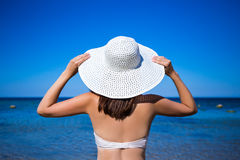 Back view of slim woman in bikini and hat looking at the sea Royalty Free Stock Images