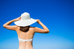 Back view of slim woman in bikini and hat over blue sky backgrou Stock Images