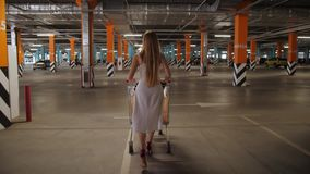 Female carrying shopping cart through parking. Back view of slim woman with long blonde hair walking with shopping cart through underground supermarket parking stock video