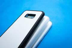 Back view of smartphone cases on vivid blue paper background. Three phone cover or protector for your design.  Black , white ,. Back view of smartphone cases on royalty free stock photos