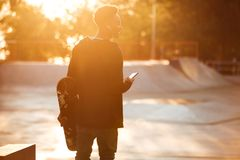 Back view of a smiling african male teenager with earphones. And mobile phone standing and holding skateboard at skate park Royalty Free Stock Photos