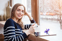Back view smiling beautiful young woman read book with digital tablet near big window in a cafe or home. Attractive Stock Photography