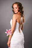 Back view of smiling young bride with a flower. On neutral studio background Royalty Free Stock Image