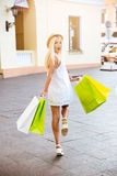 Back view of a smiling young woman with shopping bags Stock Photo