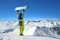 Back view of snowboarder holding board in arms raised Stock Photo