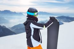 Female snowboarder  standing with snowboard in one hand and enjoying alpine mountain landscape - snowboarding concept. Back view of snowboarder with snowboard in Royalty Free Stock Photography