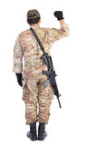 Back view of a soldier with gun holding his arm up Royalty Free Stock Photo