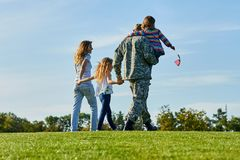 Back view soldier and his family are walking on the grass. Patriotic family with american flags, blue sky background royalty free stock image