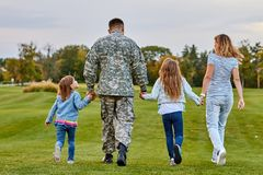 Back view soldier`s family walking. Soldier at vacation. Four family members walking together holding hands stock photos