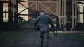 Back view of a soldier walking straight holding a rifle and a helmet in his hands. WWII reenactment. Rear view of a German soldier walking to the gates of a stock footage