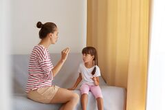 Back view of speech pathologist teaching little kid daughter right sounds pronunciation, physiotherapist working on speech defects