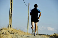 Back view sport man running on countryside track with power line poles Royalty Free Stock Image
