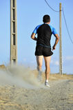 Back view sport man running on countryside track with power line poles Stock Images