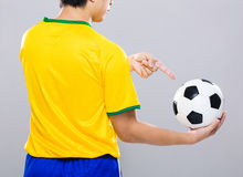 Back view of sportman finger point to soccer ball Royalty Free Stock Images