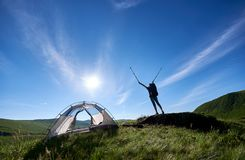 Silhouette of woman climber near camping against blue sky in the morning stock photos