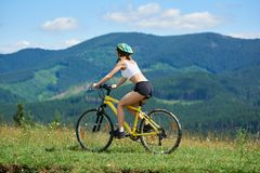 Young happy woman cycling on mountain bike at summer day stock photos