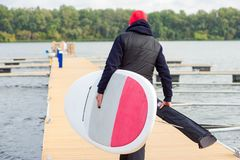 Man with stand up paddle board going to surf. Back view of sporty guy carrying surfboard and paddle in a case while walking along dock towards water in cold stock images