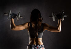 Back view of sporty sexy girl with dumbbells on a dark background. Athlete doing exercises in the gym.  Stock Photography