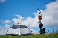 Woman hiker near camping in the mountains with backpack and trekking sticks in the morning. Back view of sporty sexy hiker with backpack near tent on the top of Stock Photos
