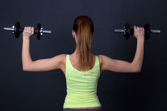 Back view of sporty woman with dumbbells over grey Royalty Free Stock Images